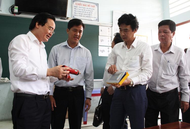 Bộ trưởng Phùng Xuân Nhạ (bìa trái)kiểm tra công tác phòng, chống Covid-19 tại Trường Tiểu học Phú Mỹ, thành phố Sa Đéc, tỉnh Đồng Tháp sáng 14/2.