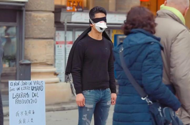 Jiang bịt mắt đứng giữa thành phố Florence,bên cạnh tấm biển Tôi không phải là một con virus, tôi là một con người, hãy giải thoát tôi khỏi định kiến.