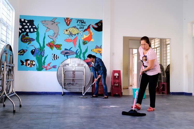 Cán bộ trung tâm dọn vệ sinh nhà bếp, nhà ăn để đón trẻ trở lại. Ảnh: Nguyễn Đông.