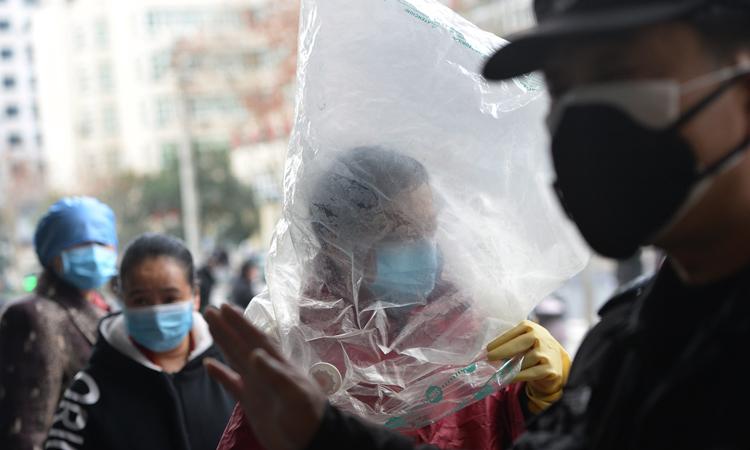 Người phụ nữ dùng túi nilon bịt đầu để tránh lây virus corona, bên ngoài siêu thị ở Vũ Hán, tỉnh Hồ Bắc, Trung Quốc. Ảnh: Zuma Press.