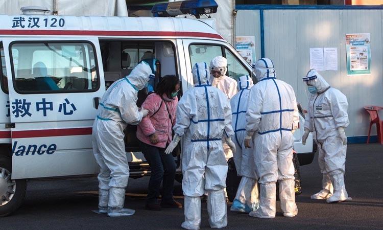 [Bệnh nhân nhiễm nCoV (áo hồng) được nhân viên y tế đưa tới bệnh viện tạm ở Vũ Hán, tỉnh Hồ Bắc. Ảnh: Zuma Press.