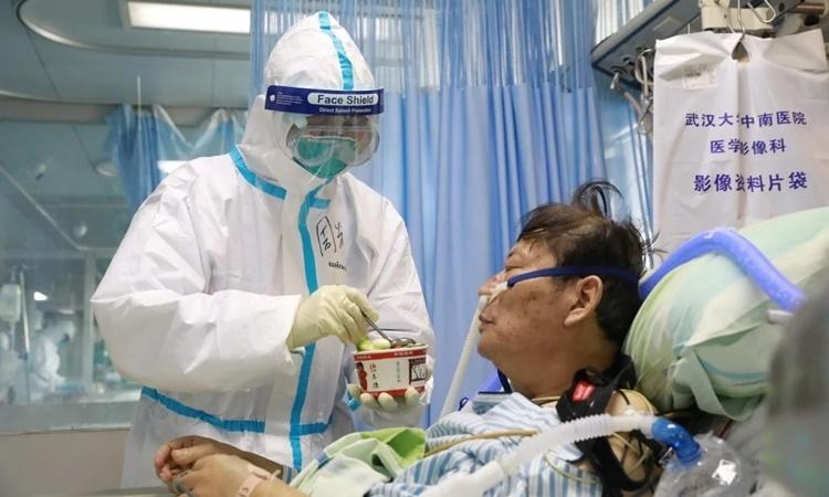 Y tá chăm sóc một bệnh nhân nhiễm nCoV tại bệnh viện ở Vũ Hán. Ảnh: Reuters.