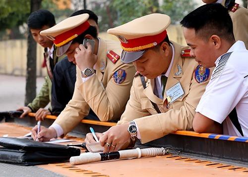Cảnh sát giao thông Hà Nội lập biên bản xử lý vi phạm hành chính với người vi phạm ở trên đường Phạm Hùng, Cầu Giấy. Ảnh: Bá Đô