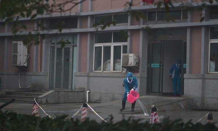 Nhân viên vệ sinh lối vào khu cấp cứu tại Trung tâm Y tế Vũ Hán hồi tháng 1. Ảnh: AP.