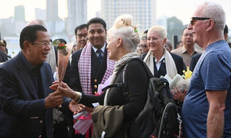 Thủ tướng Campuchia Hun Sen (trái)tặng hoa cho hành khách của du thuyền MS Westerdam hôm 14/2. Ảnh: AFP.