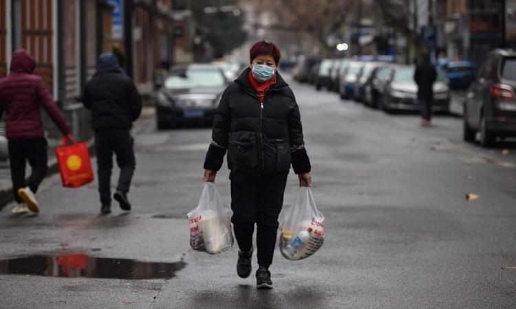 Một phụ nữ đi bộ trên đường phố Vũ Hán sau khi từ chợ về ngày 26/1. Ảnh: AFP.