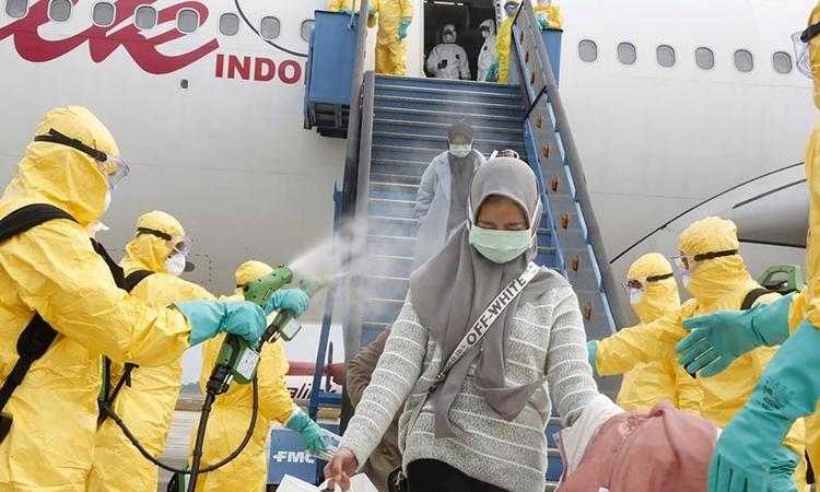 Người Indonesia sơ tán từ Vũ Hán được khử trùng khi đến đảo Natuna hôm 2/2. Ảnh: Reuters.