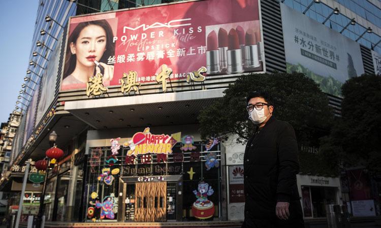 Người đàn ông đeo khẩu trang đứng bên ngoài cửa hàng mỹ phẩm đóng cửa ở Vũ Hán, tỉnh Hồ Bắc. Ảnh: Washington Post.
