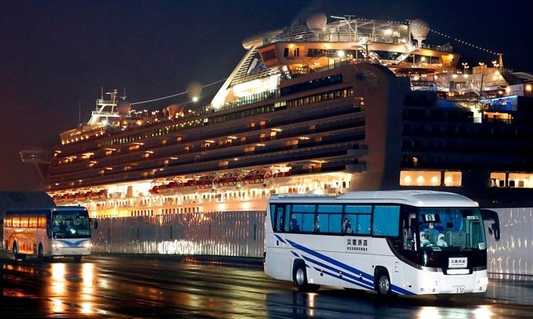 Xe buýt đưa các công dân Mỹ từ cảng Yokohama tới sân bay Haneda ở Tokyo để về nước. Ảnh: AP.