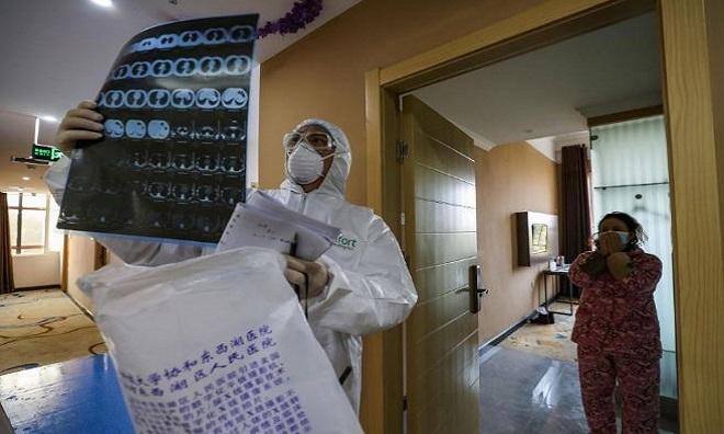 Bác sĩ xem xét phim chụp cắt lớp phổi trong khu cách ly tại một bệnh viện ở Vũ Hán hôm 3/2. Ảnh: National Geographic.