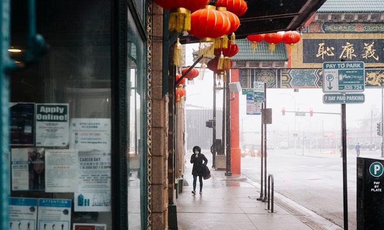 Người phụ nữ đeo khẩu trang đi bộmột mình trên phố người Hoa ở thành phố Chicago, bang Illinois. Ảnh: NY Times.