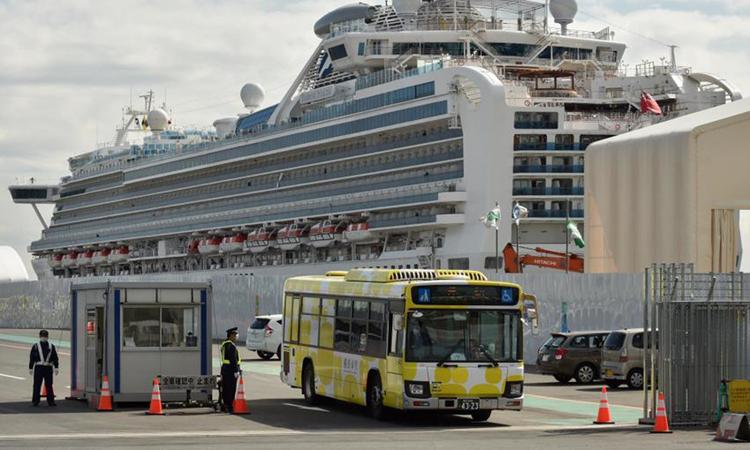 Xe buýt chở du khách rời du thuyền Diamond Princess ở cảng Yokohama hôm 19/2. Ảnh: AFP.