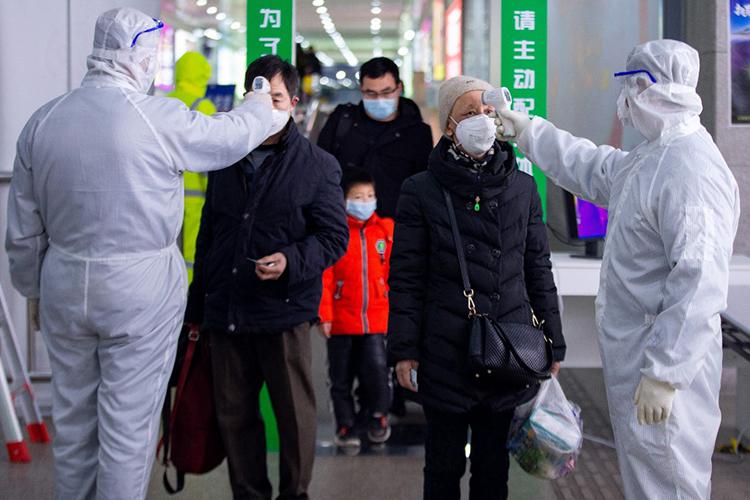 Hành khách được kiểm tra thân nhiệt tại một ga tàu ở Nam Kinh, tỉnh Giang Tô hôm 18/2. Ảnh: AFP