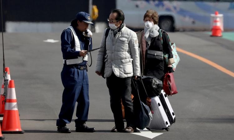 Hành khách rời du thuyền Diamond Princess tại cảng Yokohama ngày 19/2. Ảnh: Reuters.