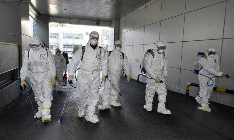 Nhân viên y tế phun thuốc khử trùng trước nhà thờ Tân Thiên Địa ở Daegu, Hàn Quốc hôm 19/2. Ảnh: AFP.