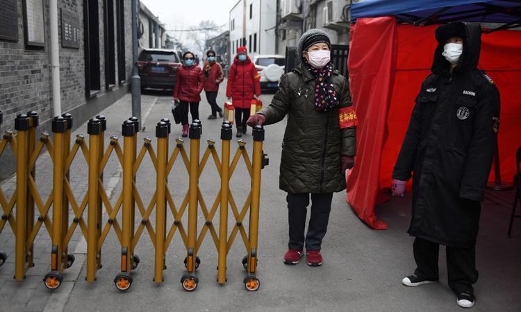 Nhân viên bảo vệ cùng cư dân đứng gác tại một trạm kiểm soát ở Bắc Kinh, Trung Quốc hôm 20/2. Ảnh: AFP.