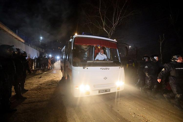 Xe buýt chở hơn 70 người được sơ tán về từ Vũ Hán di chuyển dưới sự bảo vệ của cảnh sát tại Novi Sanzhary, vùng Poltava, miền trung Ukraine, hôm qua. Ảnh: AFP.
