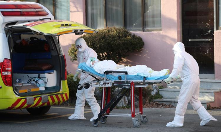 Nhân viên y tế đưa một ca nghi nhiễm nCoV tại Cheongdo, Hàn Quốc tới bệnh viện khác hôm 21/2. Ảnh: AFP.