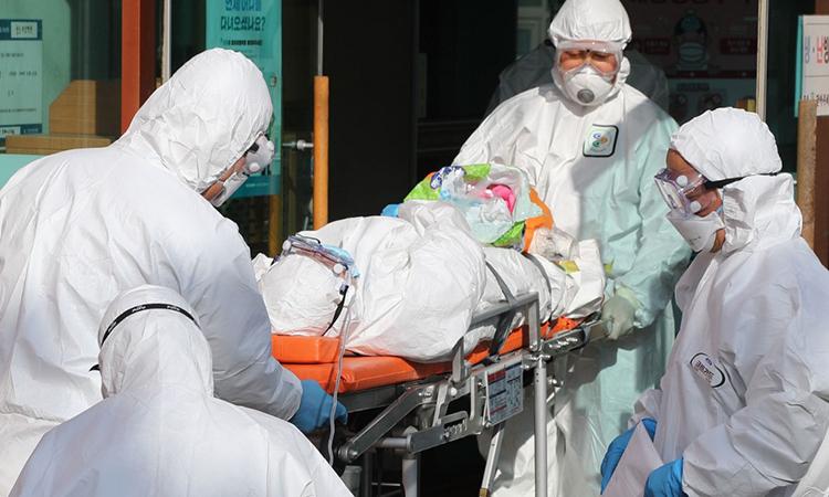 Nhân viên y tế mặc đồ bảo hộ chuyển một bệnh nhân nghi nhiễm virus corona (nằm trên cáng) từ bệnh viện Daenam tới một bệnh viện khác ở thành phố Cheongdo ngày 21/2. Ảnh: AFP.