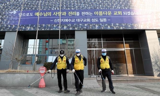 Nhân viên vệ sinh khử trùng khu vực trước chi nhánhcủa giáo phái Shincheonji tại Daegu ngày 20/2. Ảnh: AFP.