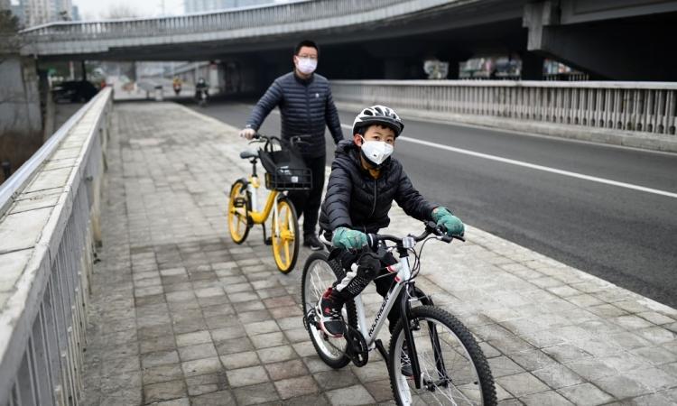 Người dân Bắc Kinh đeo khẩu trang khi đi trên đường phố hôm 20/2. Ảnh: AFP.