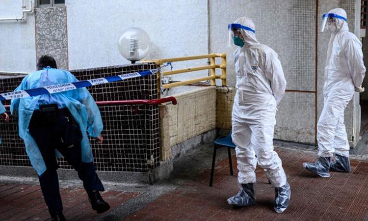 Cảnh sát Hong Kong mặc đồ bảo hộ bên ngoài tòa nhà Hong Mei House ở Hong Kong hôm 11/2, sau khi tòa nhà xuất hiện ca nhiễm nCoV. Ảnh: AFP.