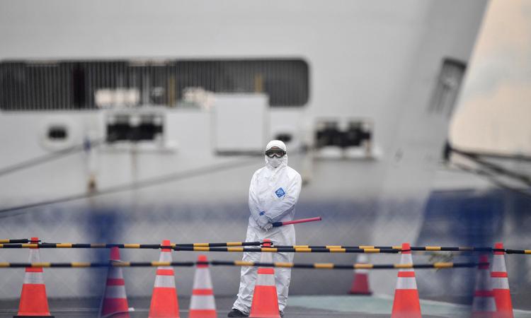 Một quan chức mặc đồ bảo hộ đứng gần du thuyền Diamond Princess ở cảng Yokohama, Nhật Bản hôm 20/2. Ảnh: AP.