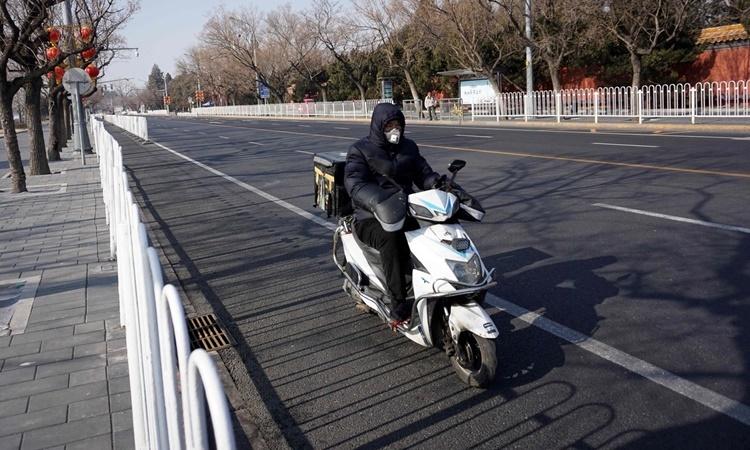 Một nhân viên giao hàng ở Bắc Kinh ngày 31/1. Ảnh: AFP.