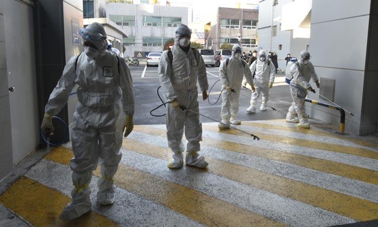 Nhân viên y tế khử trùng trước nhà thờ của giáo phái Tân Thiên Địa ở Daegu, Hàn Quốc hôm 19/2. Ảnh: AFP.