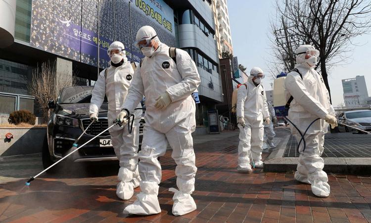 Nhân viên mặc đồ bảo hộ phun thuốc khử trùng ở thành phố Daegu hôm 20/2. Ảnh: AP.