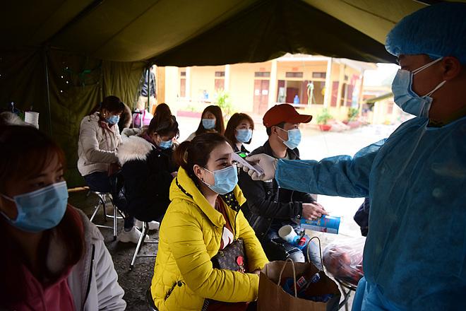 Người về từ Trung Quốc được cách ly tại Lạng Sơn và kiểm tra thân nhiệt. Ảnh: Giang Huy.