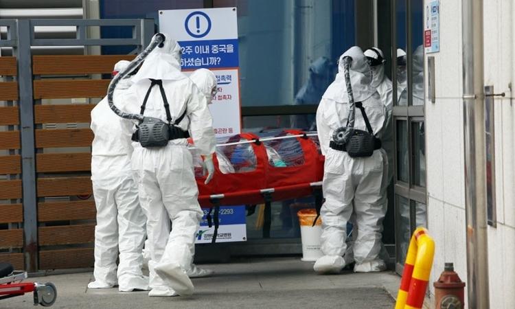 Nhân viên y tế đưa bệnh nhân nCoV vào bệnh viện ở Chuncheon ngày 22/2. Ảnh: AFP.
