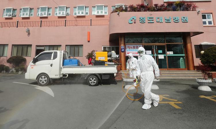 Nhân viên y tế mặc đồ bảo hộ phun hóa chất tẩy trùng trước bệnh viện đang điều trị cho 16 bệnh nhân nhiễm nCoV tại thành phố Daegu, Hàn Quốc ngày 21/2. Ảnh: AFP.