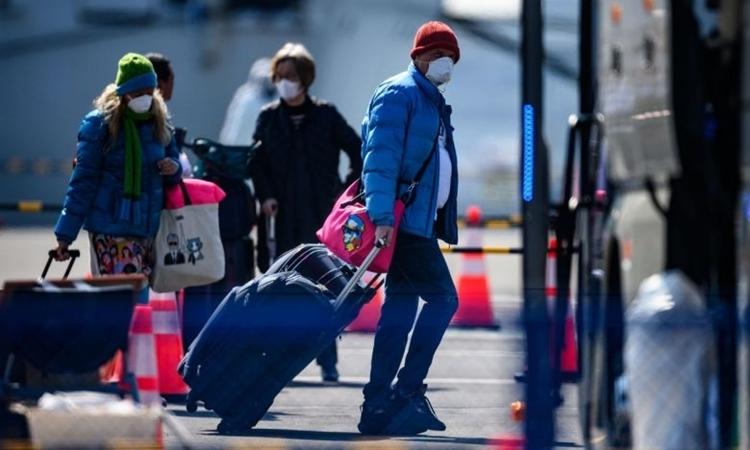 Hành khách rời khỏi tàu Diamond Princess ngày 21/2. Ảnh: AFP.