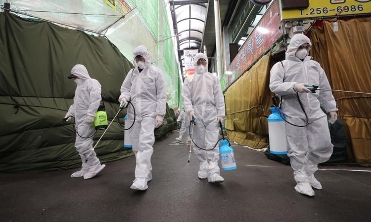 Nhân viên y tế tẩy trùng một khu chợ ở Daegu ngày 23/2. Ảnh: AFP.