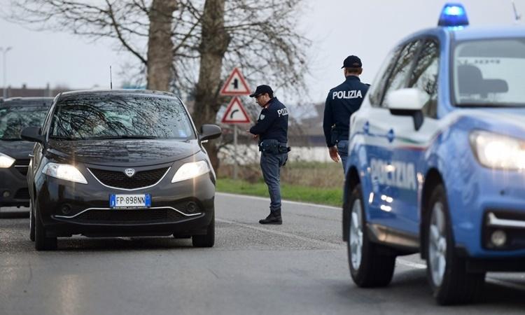 Cảnh sát kiểm tra một chiếc xe tại lối vào thị trấn Casalpusterlengo, đông nam thành phố Milan, Italy, ngày 23/2. Ảnh: AFP.