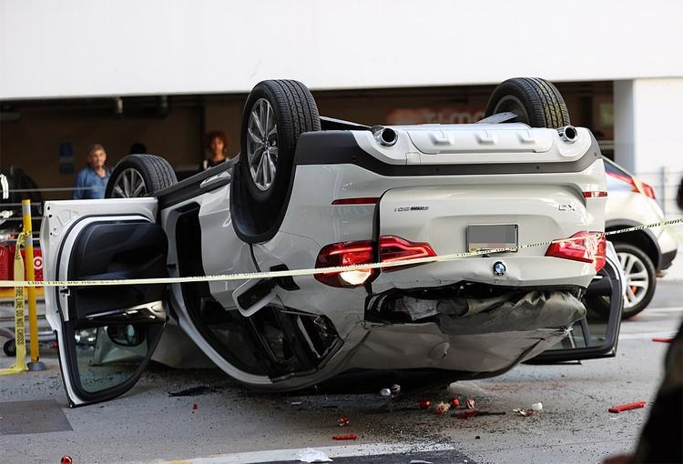 Chiếc BMW màu trắng tiếp đất bằng nóc, dập móp nhiều chỗ. Ảnh: Backgrid