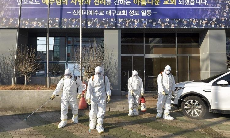 Nhân viên y tế tẩy trùng phía trước nhà thờ giáo phái Tân Thiên Địa ở Daegu, Hàn Quốc hôm 19/2. Ảnh: AP.