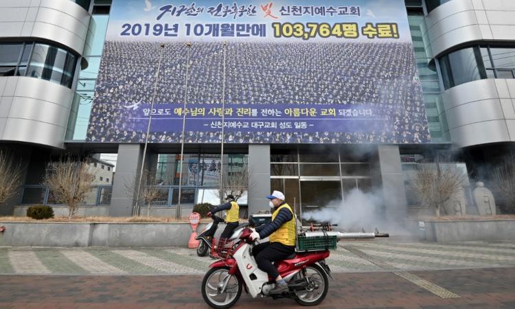 Nhân viên y tế khử trùng khu vực trước trụ sở Tân Thiên Địa ở Daegu hôm 21/2. Ảnh: AFP.