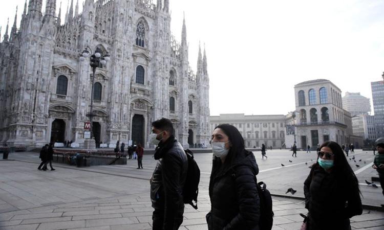 Người dân đeo khẩu trang khi đi qua nhà thờ Duomo ở thành phố Milan, miền bắc Italy hôm 23/2. Ảnh: AP.