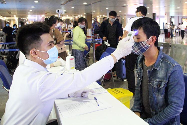 Nhân viên Trung tâm kiểm dịch quốc tế đo thân nhiệt hành khách tại sân bay Tân Sơn Nhất. Ảnh: Hữu Nguyên