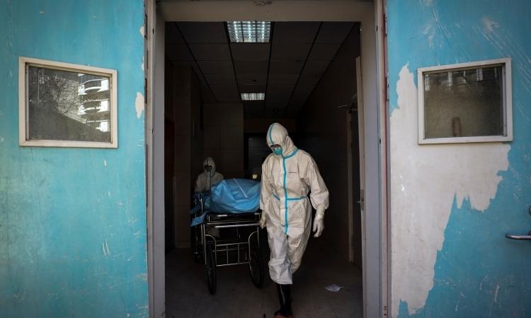 Nhân viên y tế di chuyển thi thể một bệnh nhân tử vong vì virus corona tại bệnh viện ở Vũ Hán hôm 16/2. Ảnh: AP.