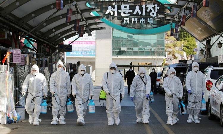 Nhân viên y tế tẩy trùng tại một khu chợ ở thành phố Daegu, phía đông nam Hàn Quốc hôm 23/2. Ảnh: AFP.