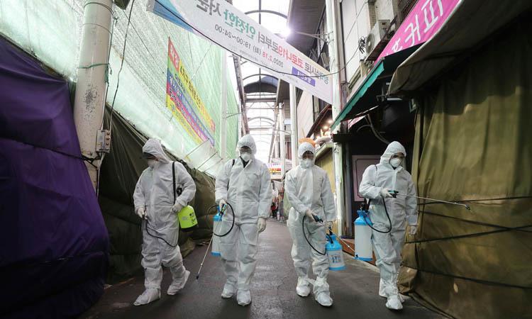 Nhân viên y tế phun thuốc khử trùng khu chợ ở thành phố Daegu hôm 23/2. Ảnh: AP.