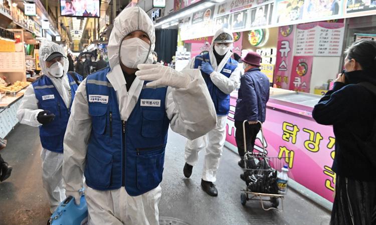 Nhân viên kiểm dịch Hàn Quốc phun thuốc khử trùng tại một khu chợ ở thủ đô Seoul hôm nay. Ảnh: AFP.
