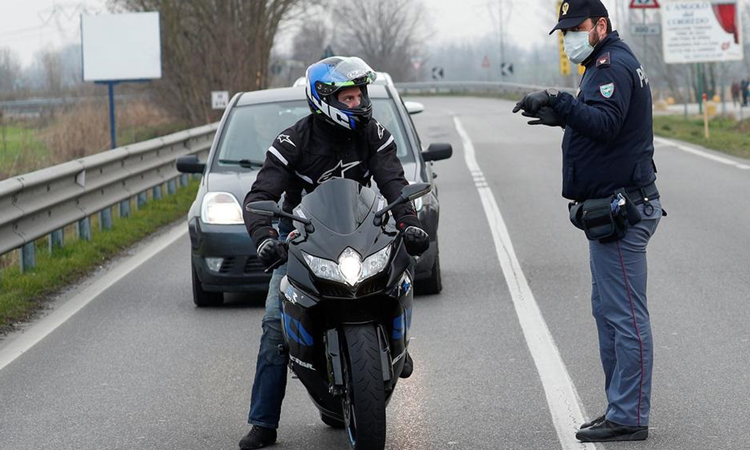Cảnh sát đeo khẩu trang cảnh báo người đi đường về dịch Covid-19 tại Casalpusterlengo, vùng Lombardy hôm 23/2. Ảnh: Reuters.