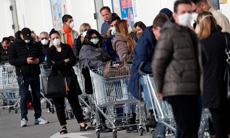 Người dân xếp hàng dài bên ngoài siêu thị ở Casalpusterlengo, vùng Lombardy hôm 23/2. Ảnh: Reuters.