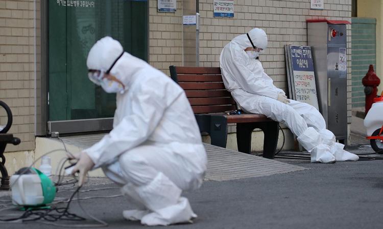 Một nhân viên y tế mặc đồ bảo hộ tranh thủ nghỉ ngơi trong lúc chờ xe cứu thương chở bệnh nhân nhiễm nCoV tại lối vào một bệnh viện ở Daegu hôm 23/2. Ảnh: AFP.