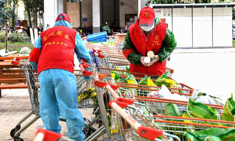 Hai nhân viên tổ dân phố ở thành phố Vũ Hánchuẩn bịthực phẩm giao cho cư dân. Ảnh: AFP.