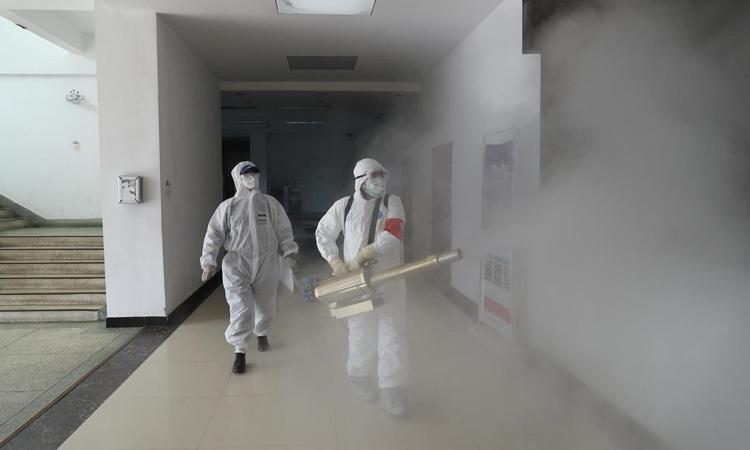 Hai nhân viên y tế phun thuốc khử trùng cho một chung cư ở Vũ Hán hôm 22/2. Ảnh: Reuters.